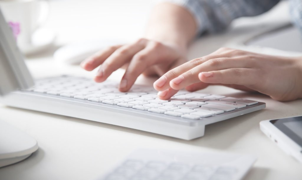 Hands typing on a white keyboard inside the office.