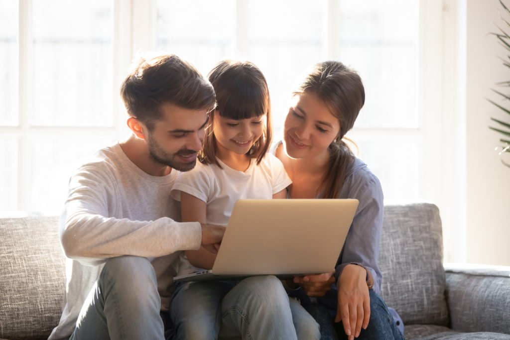Happy family on a couch using a laptop.