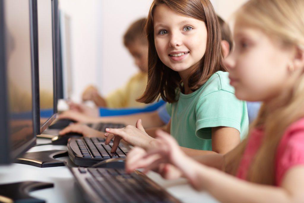 Happy schoolgirl child using a computer.