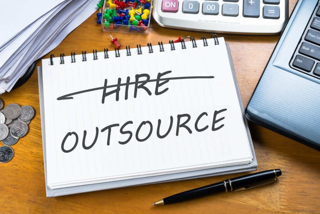 Outsource memo in notebook with part of laptop, receipts and calculator.