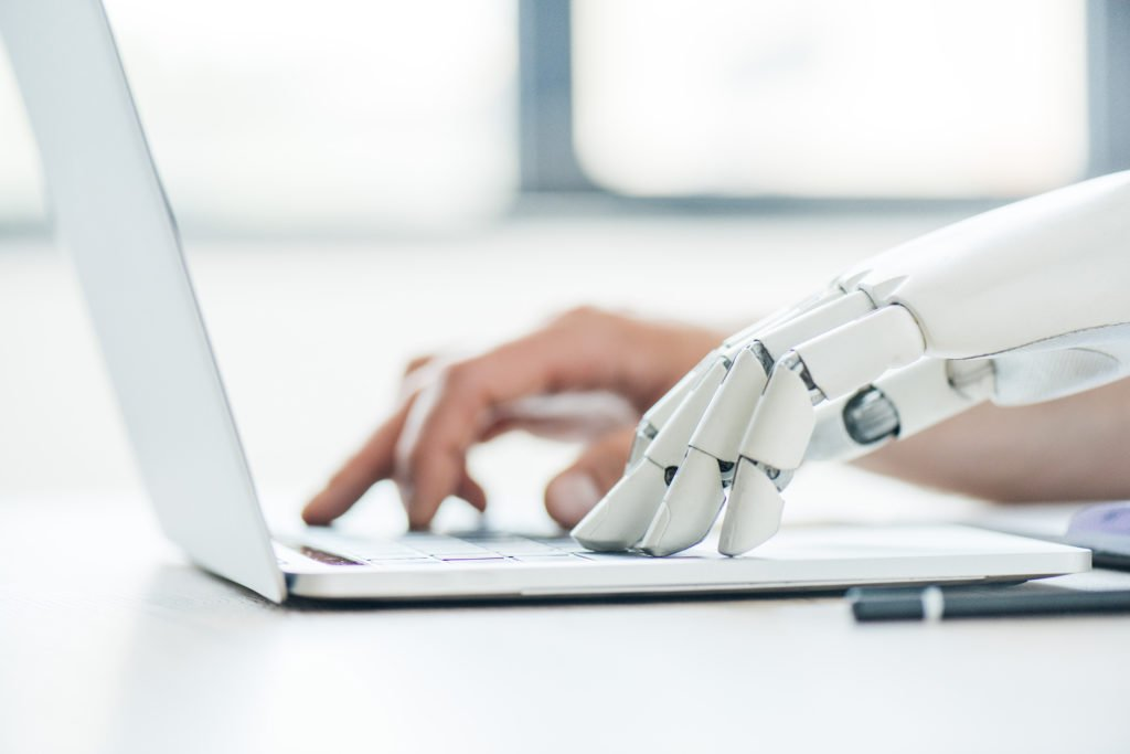 Focus of human and robot hands typing on laptop.