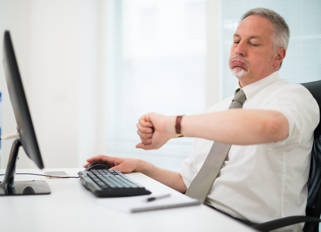 Impatient employee watching his wrist watch in the office.