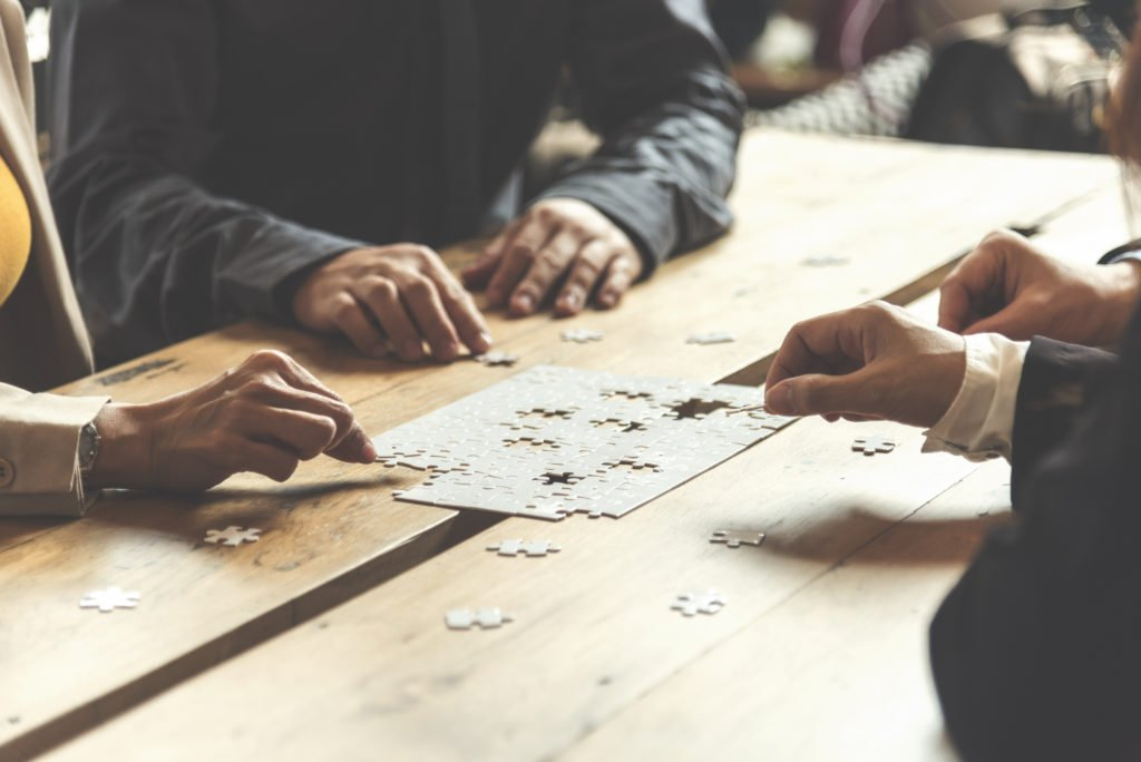 Implement improve puzzel solve connections together with synergy strategy team building organizing connection by trust communication. Hands of stakeholders business trust team holding jigsaw puzzle.