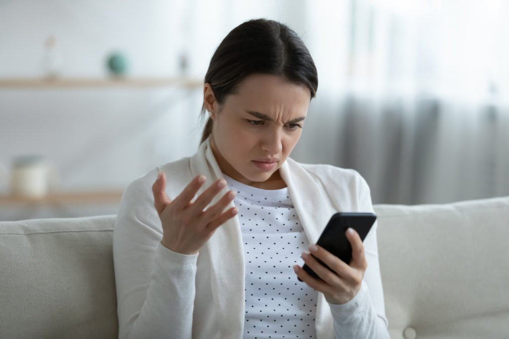 Irritated woman holding smartphone having problems with gadget feels annoyed