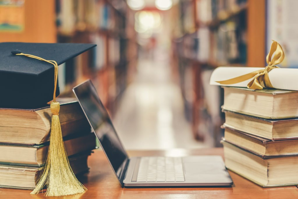 E-learning class and internet online education success with IT computer laptop, graduation hat, academic cap, mortarboard and degree certificate on books in class or library study room.