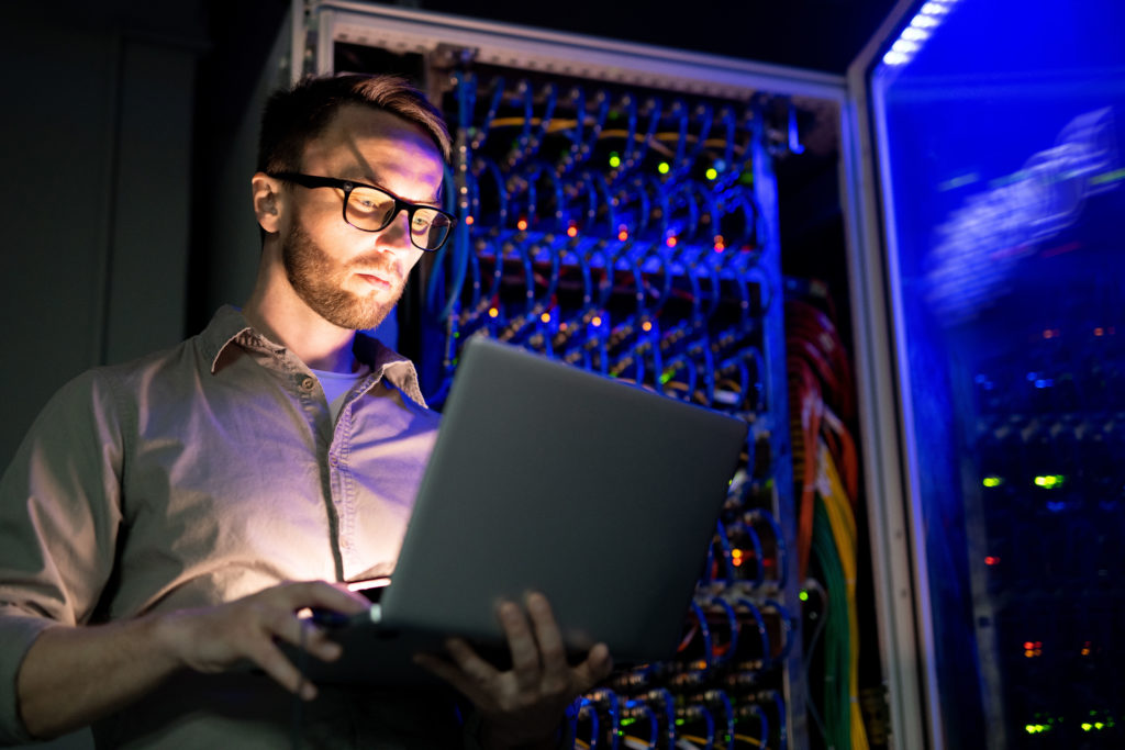 IT engineer standing near the network servers.