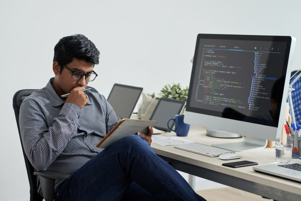 IT engineer thinking in front of computer codes.