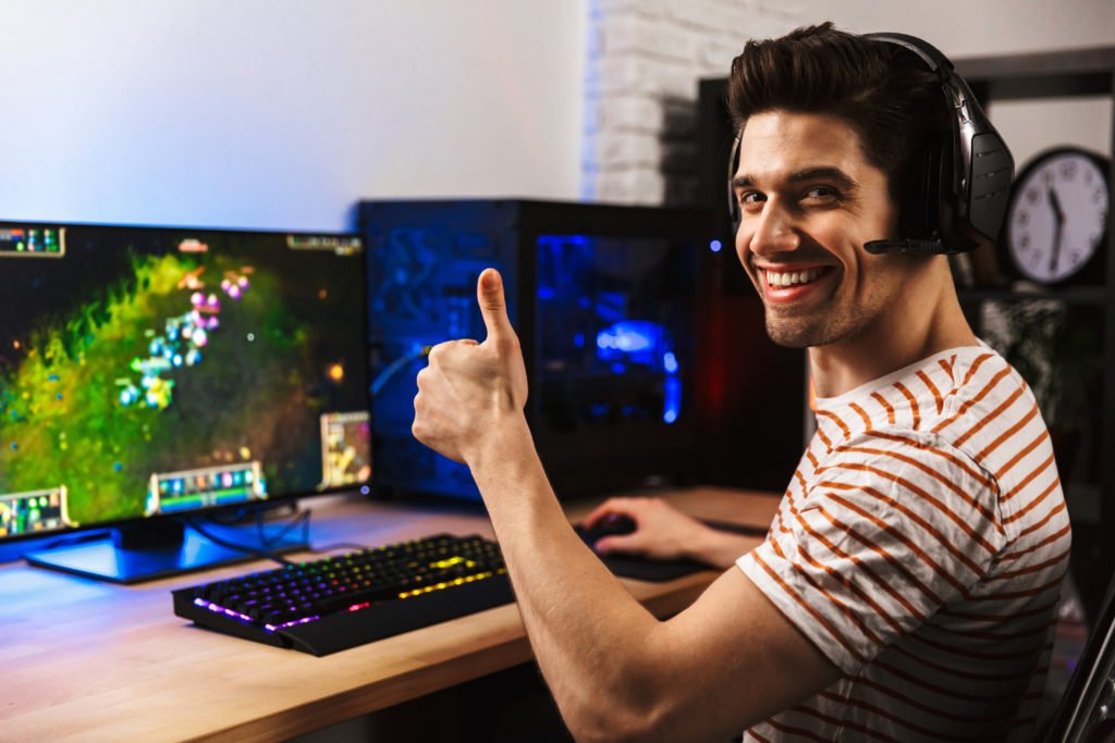Joyful gamer guy with his thumbs up, playing video games on his computer.