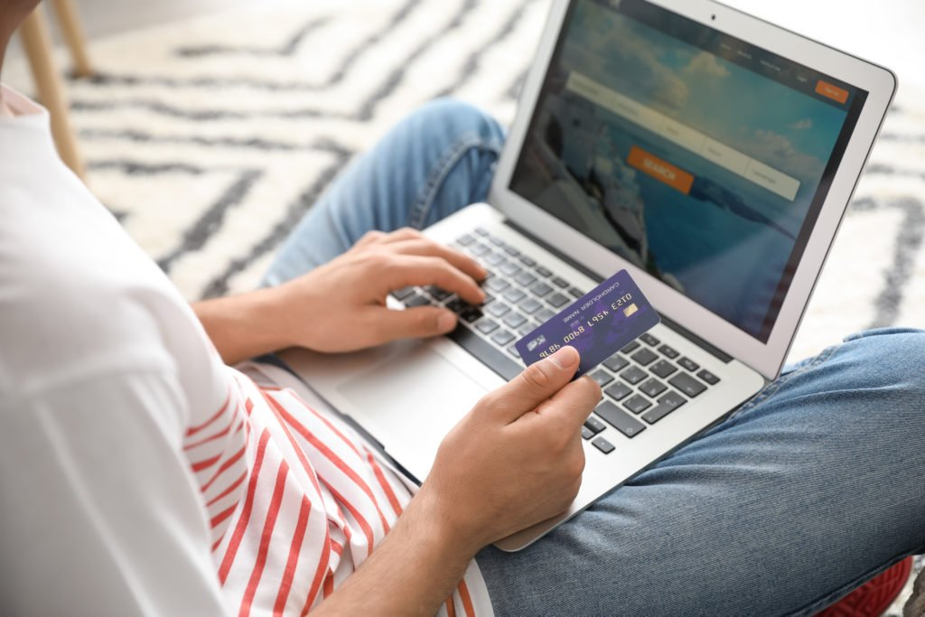 Using laptop in booking tickets online with credit card.