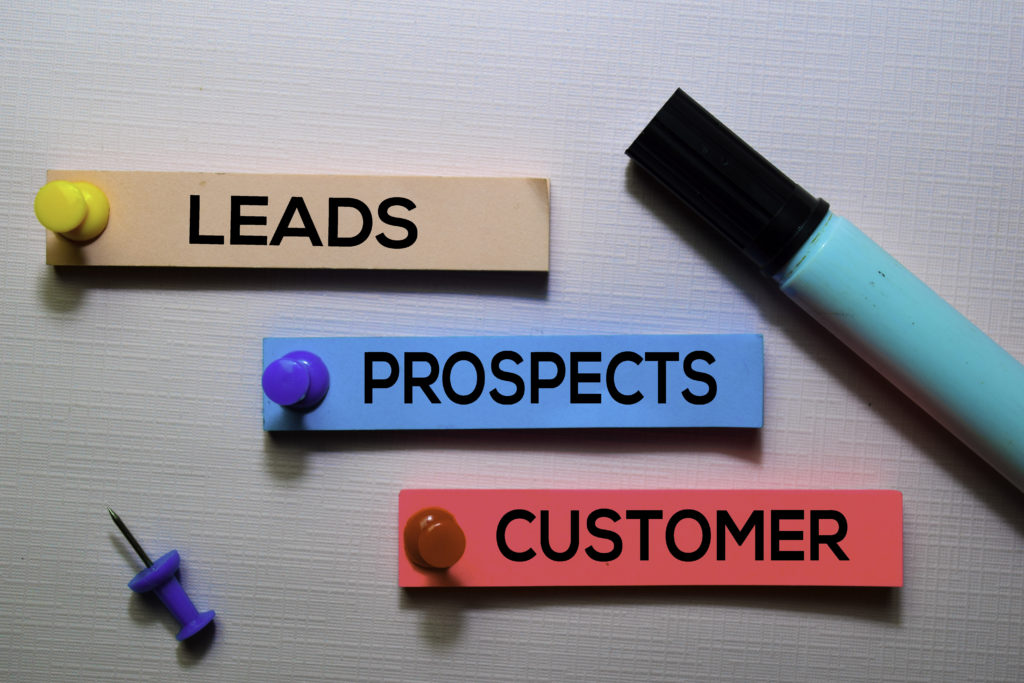 Leads, Prospects, Customer text on sticky notes isolated on office desk.