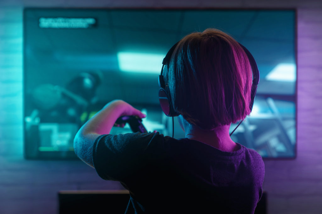 Little boy playing video game in a dark room.