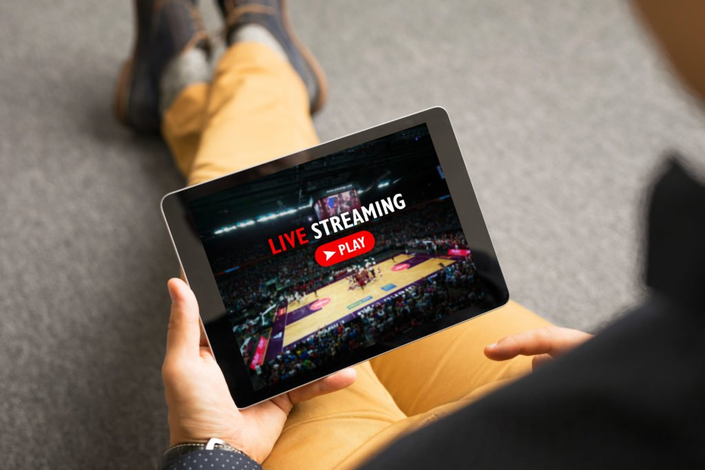 Man live streaming sports show on tablet.