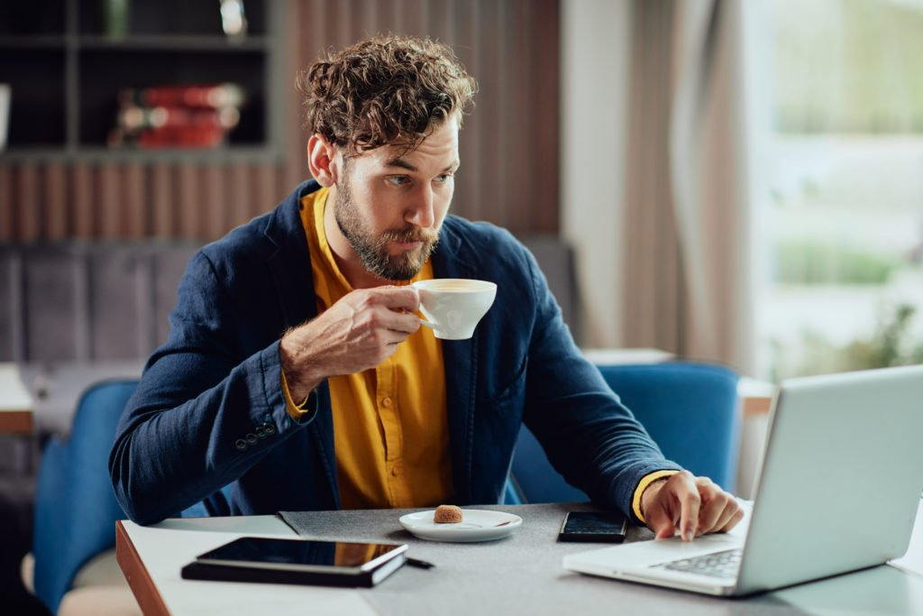 Entrepreneur drinking espresso and using laptop in coffee shop.