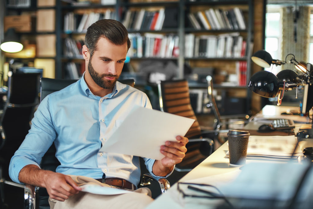 Man examining documents inside the office.