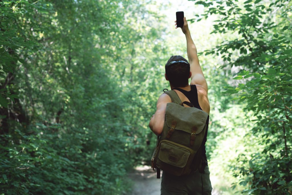 Man in a forest with his phone having no signal.