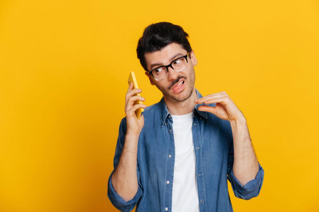 Man ignoring a phone conversation while making 'blah blah' gestures, orange background.