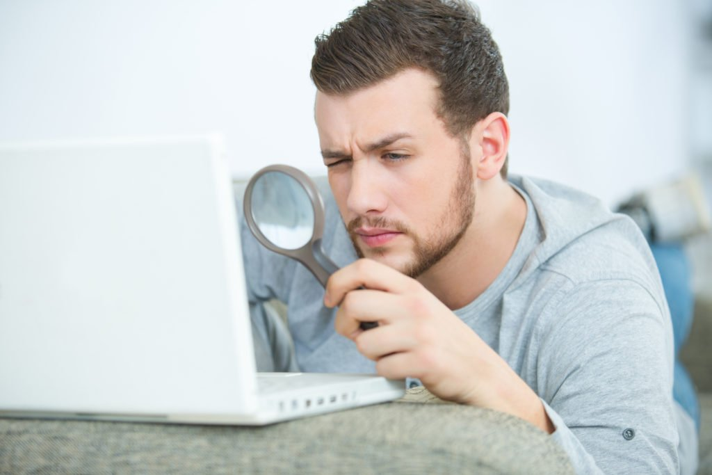 Man looking through a magnifying glass to his laptop.