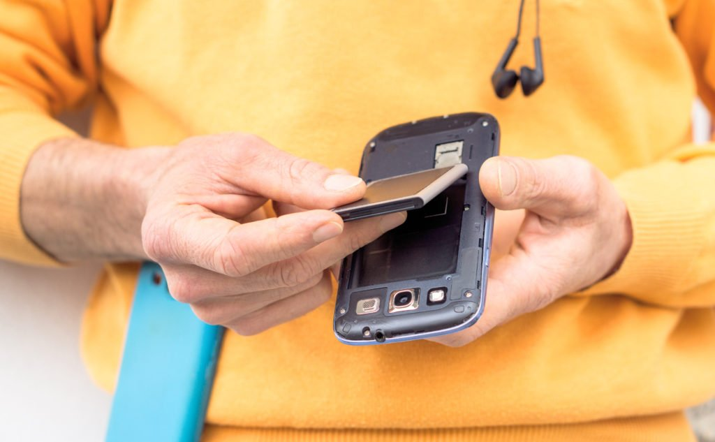 Man in orange shirt placing battery on a phone.