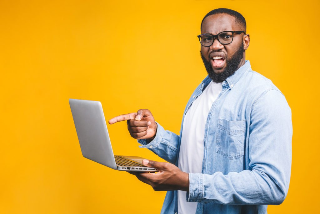 Man pointing at his laptop, against yellow background.