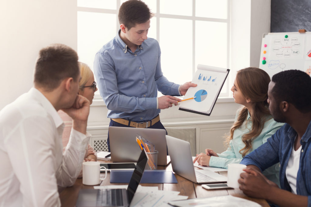 Man presenting charts to his colleagues.