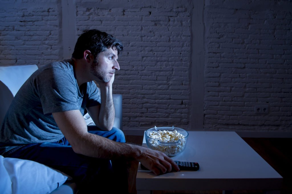 Man sitting on a sofa while watching television and eating popcorn at night.