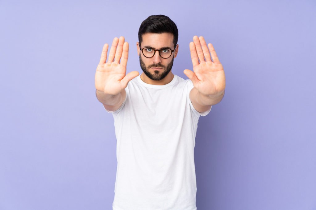 Man doing a 'stop' sign with his hands, blue background.