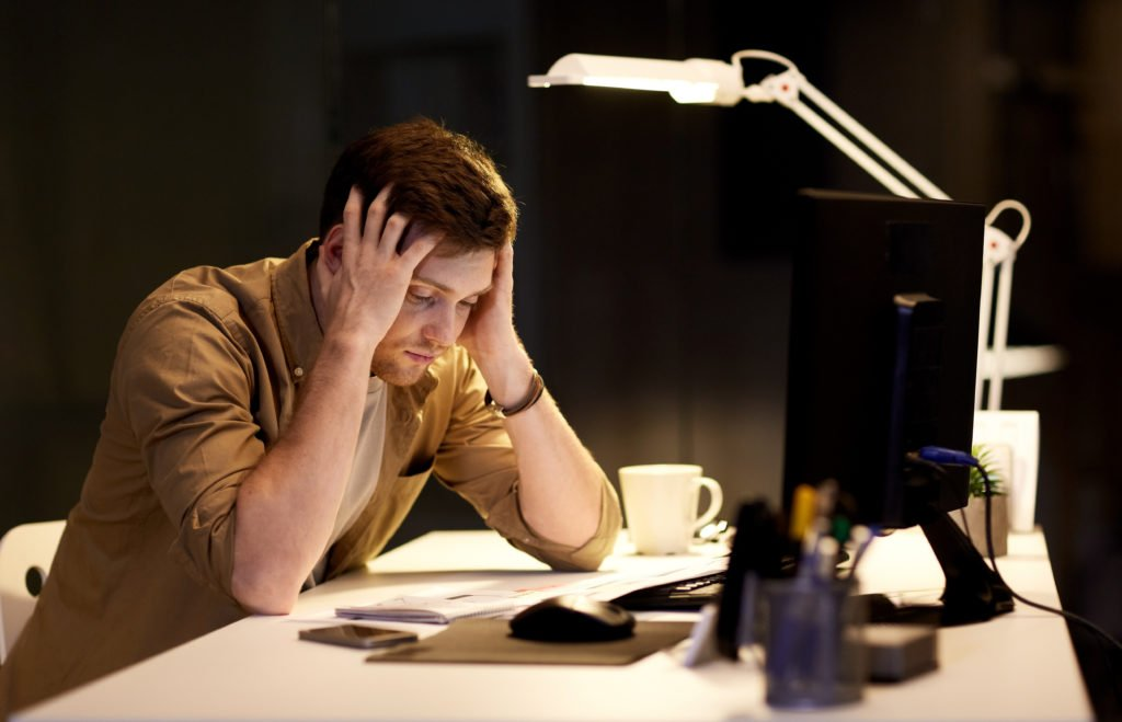 Man stressed while working late at night in the office.