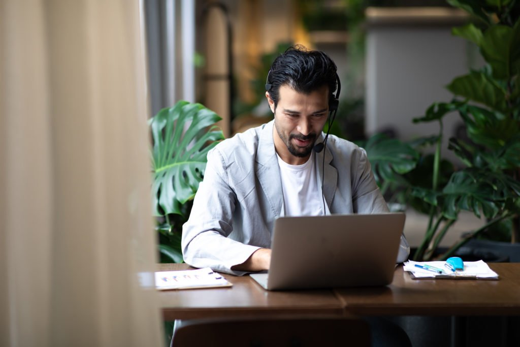 Man in suits and headsets smiling while working with his laptop inside modern office.