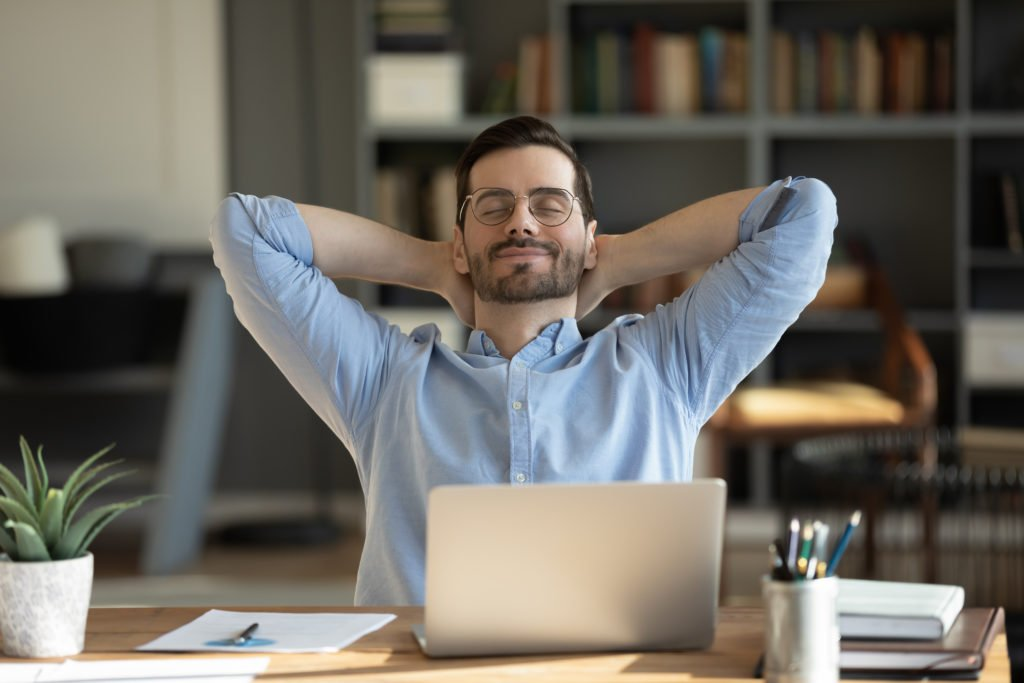 Man takes a break from his work and laptop, leans back on chair.