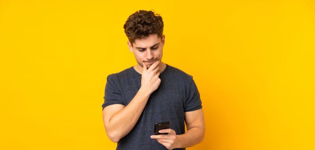 Man thinking while looking at his phone, yellow background.