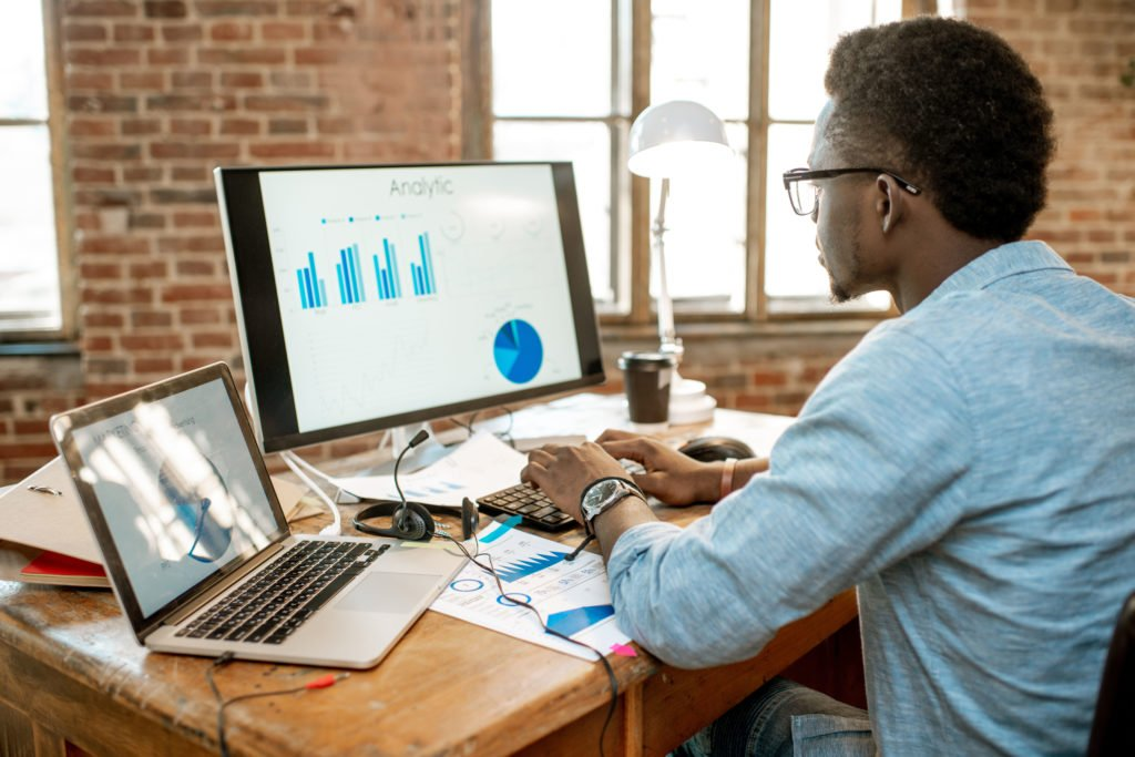 Man working with analytics, using desktop computer and laptop.