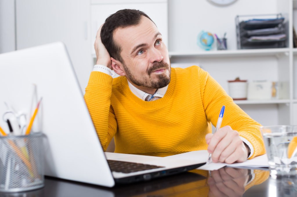 Man in yellow shirt thinking in front of his laptop.