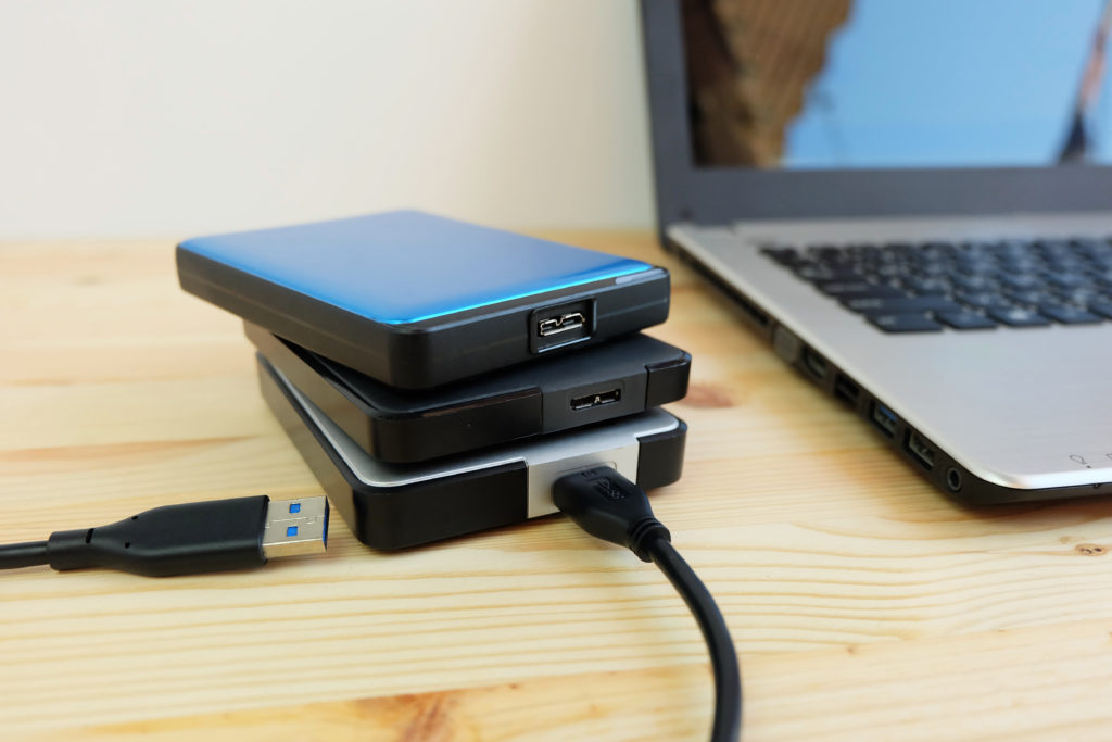 Many portable external hard drives stacked on wooden table.