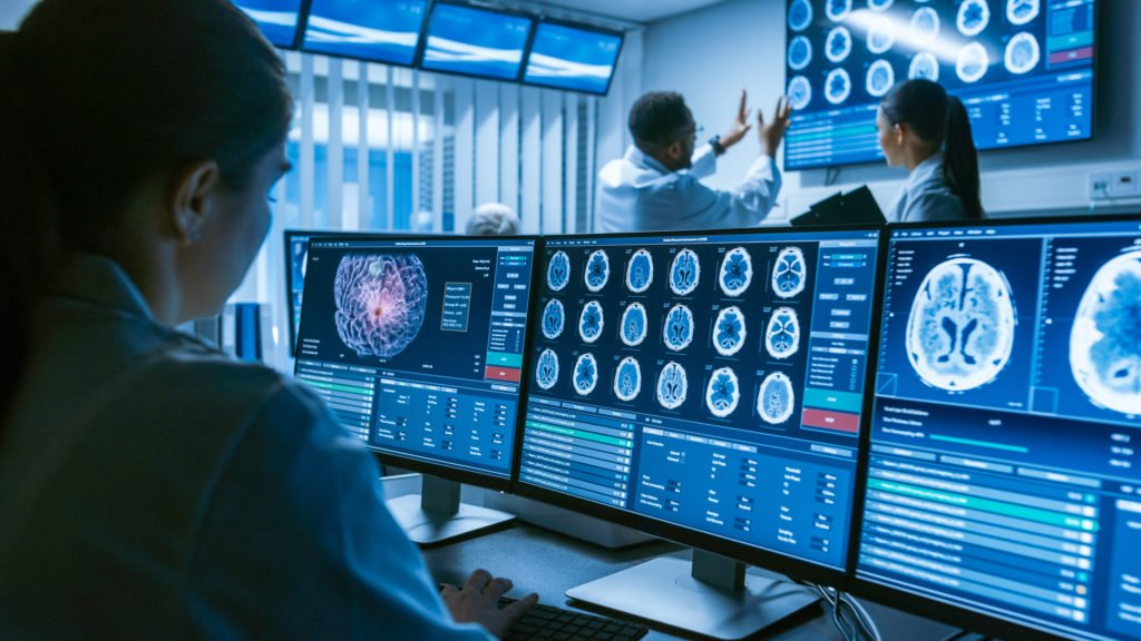 Medical scientist working with brain scans on computer screens inside the laboratory.