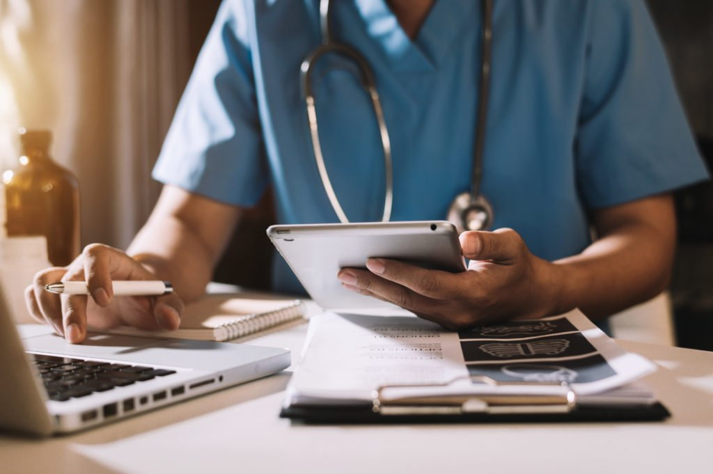Medical technology concept, doctor using his tablet and laptop.