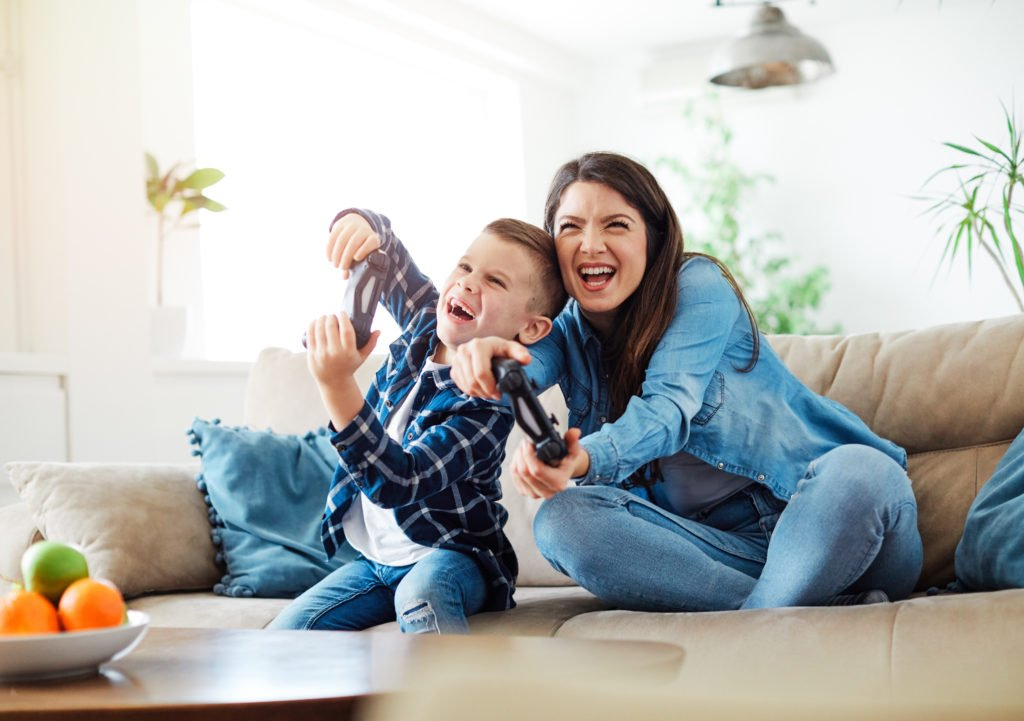 Mother and son playing console games at home.