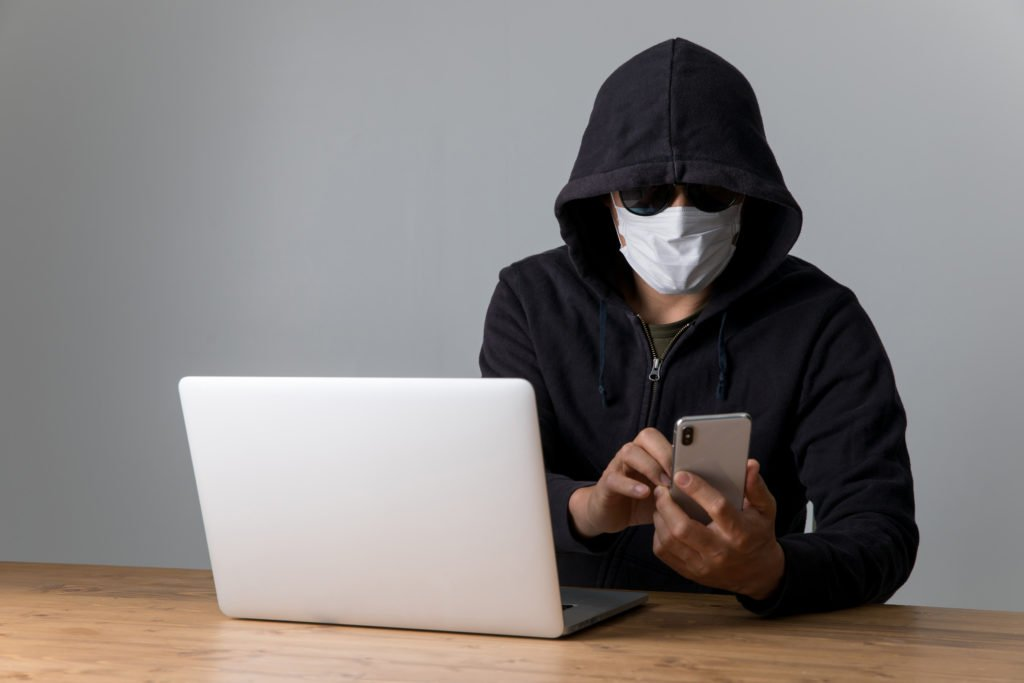 Mysterious person in a hooded jacket using phone and laptop.
