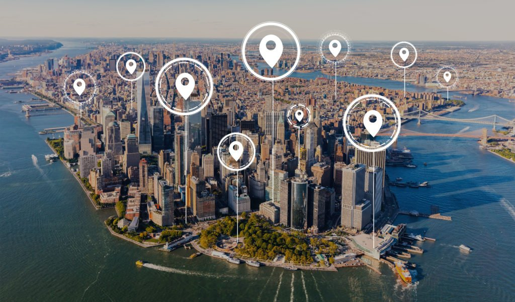 Map pins with aerial view of Manhattan, New York skyline.
