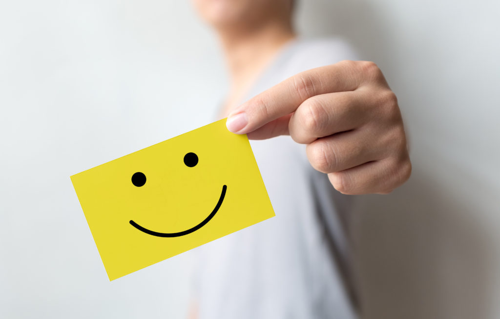 Customer service experience and business satisfaction survey. Man holding yellow card with smiley face.