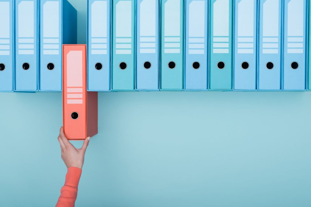 Office worker taking an highlighted folder in the archive: database, administration and file management concept.