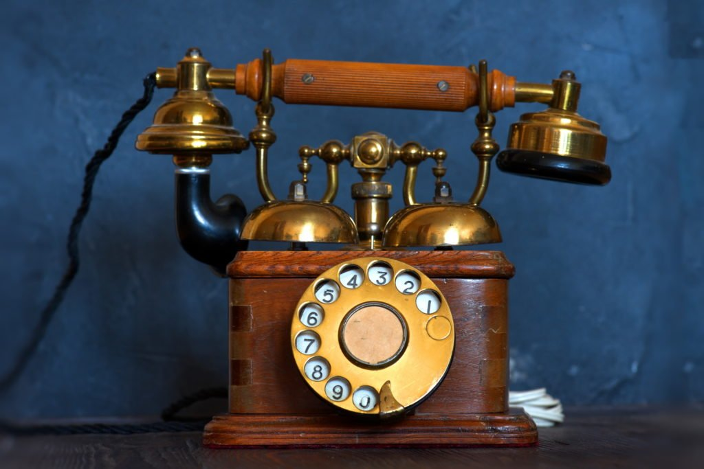 Old vintage telephone with blue background.