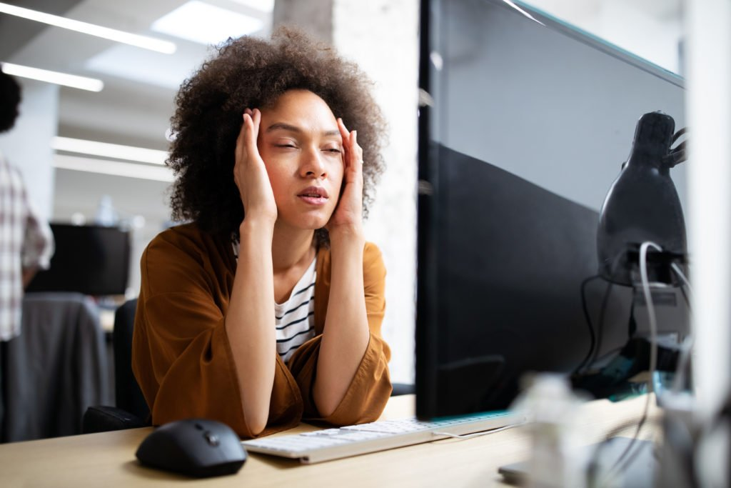 Overworked woman looking stressed in front of a computer in the office.