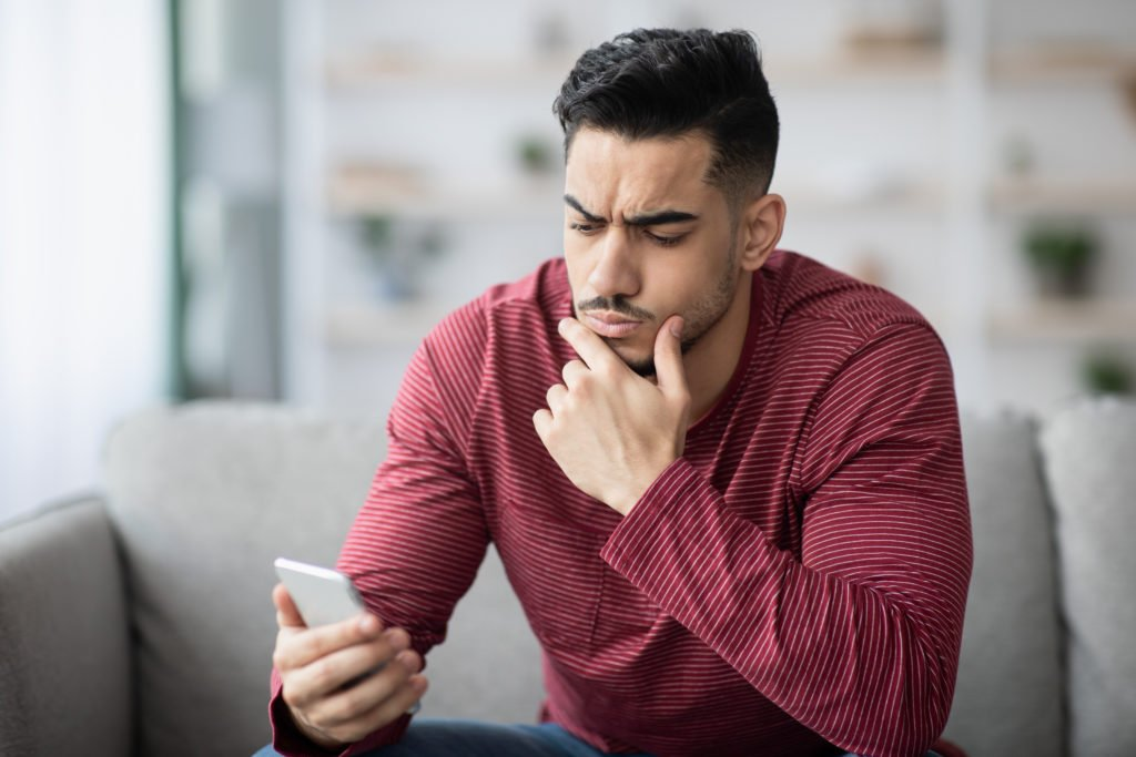 Pensive guy in red shirt using his phone.