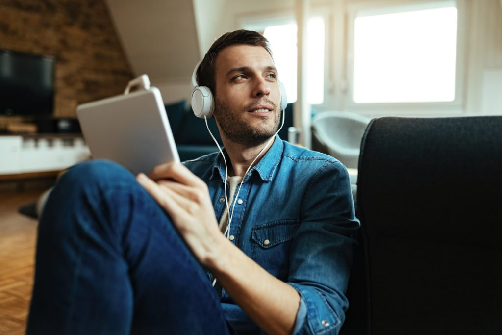 Pensive man in headphones while using his tablet.