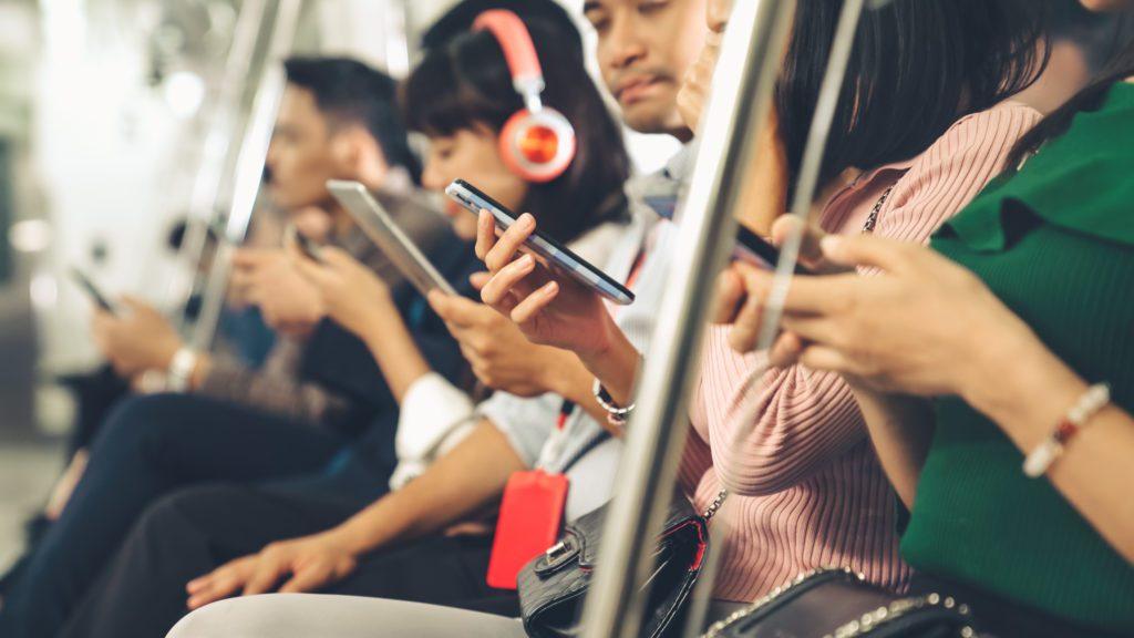 People using mobile phones in public underground train.