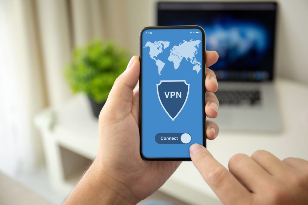 Man holding phone with blue vpn application.