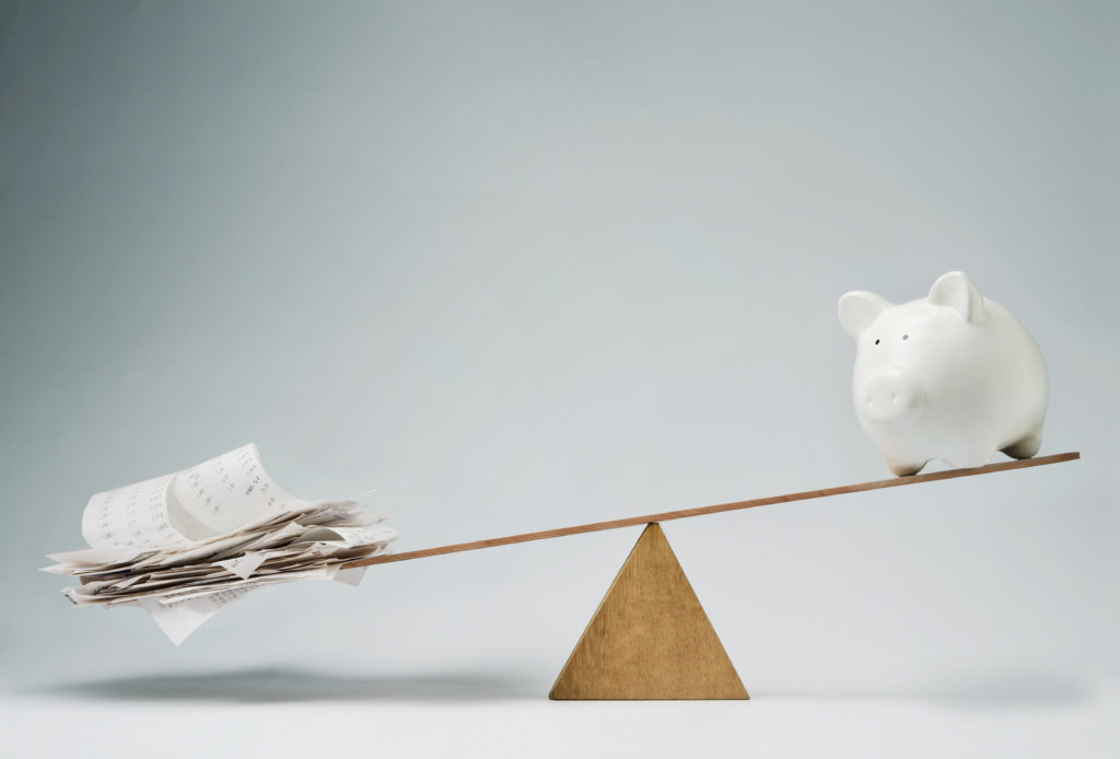 Piggy bank balancing on seesaw over a stack of bills.