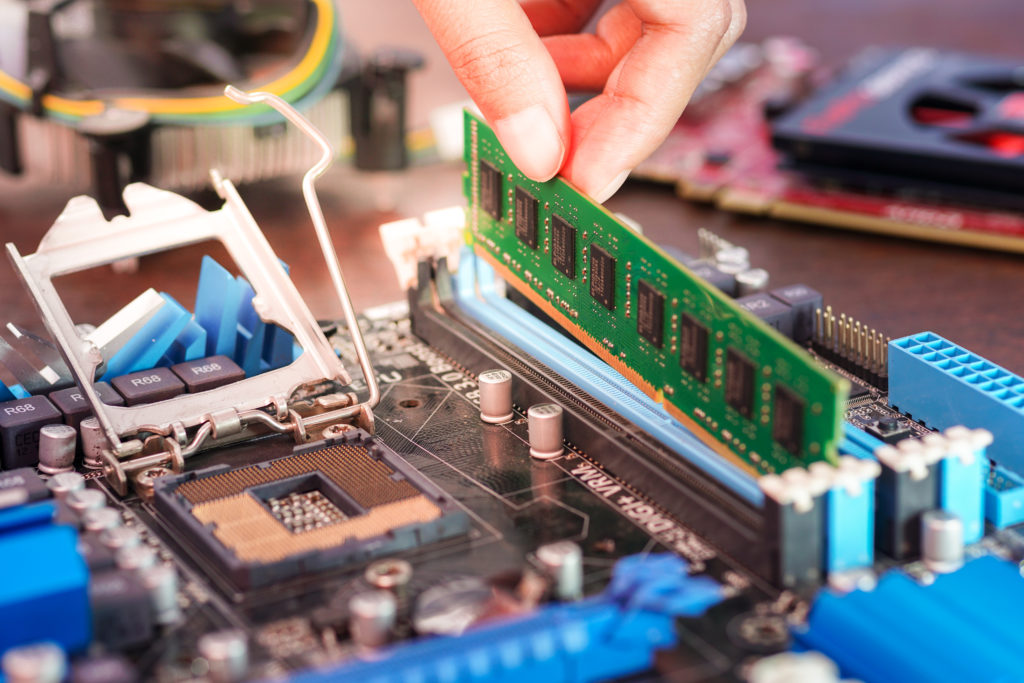 Placing RAM on the socket of computer motherboard.