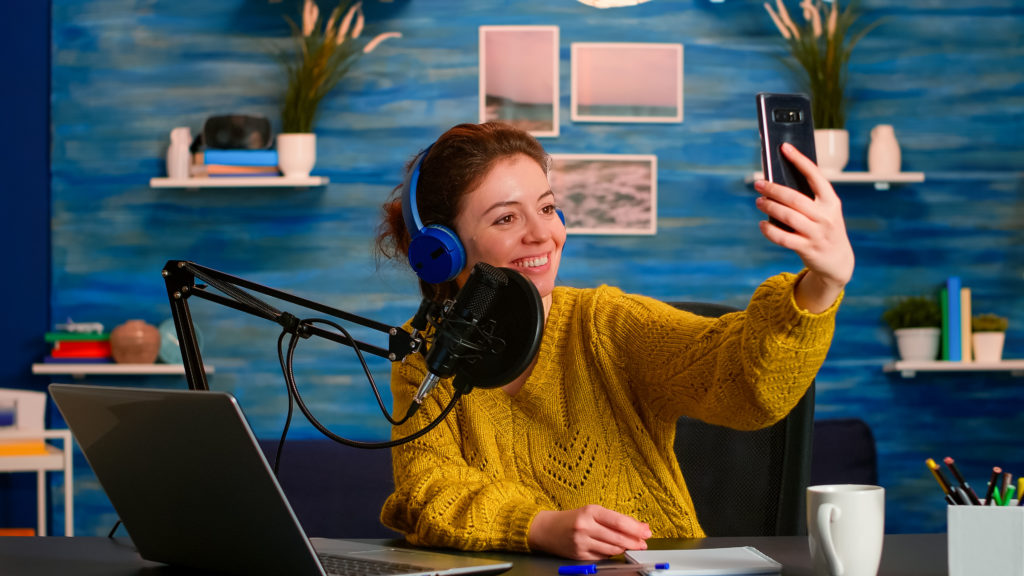 Podcaster taking a selfie while on-air inside her studio.