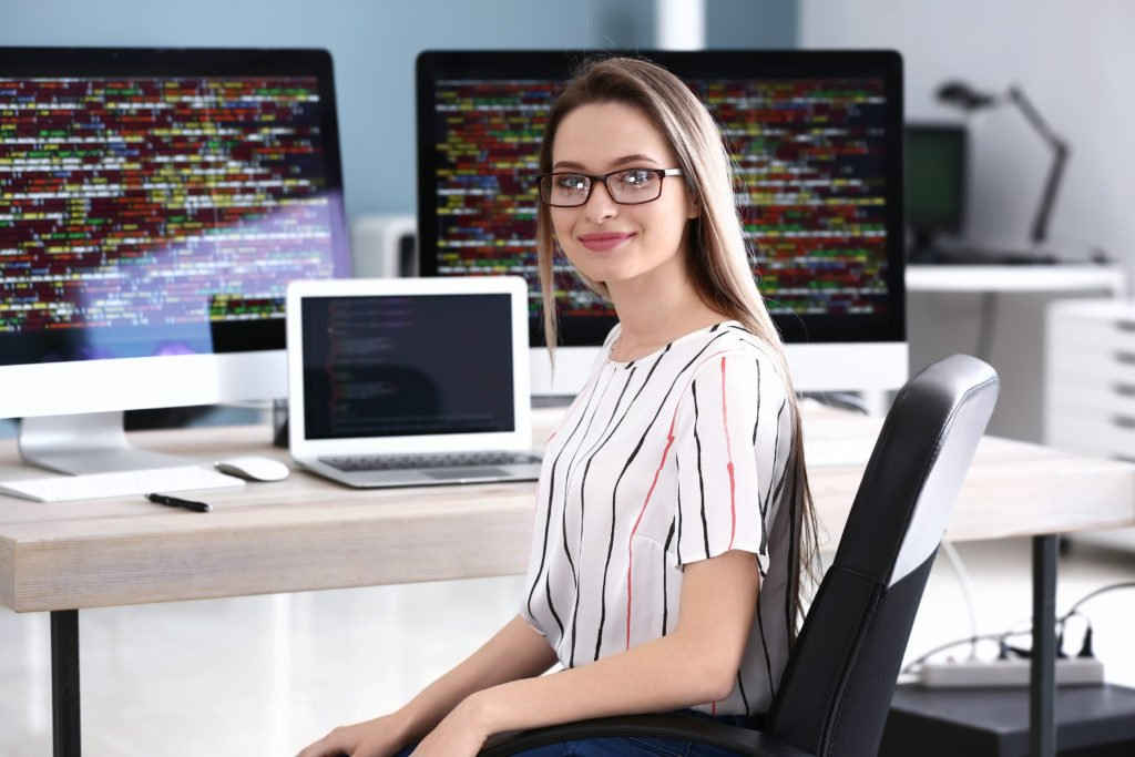 Portrait of a female programmer with several computers.